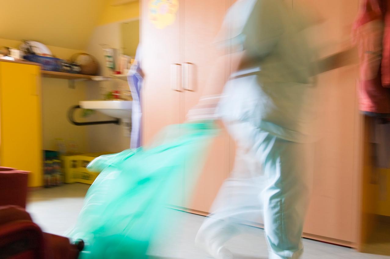 Nicole Spiegel ist eine Bewohnerin des Jakob-Riedinger-Hauses in Würzburg, einem Wohn- und Wohnpflegeheim für Menschen mit Behinderung. Der Bezirk Unterfranken hat sich die psychiatrische und neurologische Versorgung der unterfränkischen Bevölkerung zur wichtigsten gesundheitspolitischen Aufgabe gemacht. Sie zeigt, wie sie in ihren Tag startet. Eine Reinigungskraft putzt das Zimmer von Nicole und ihrer Mitbewohnerin.