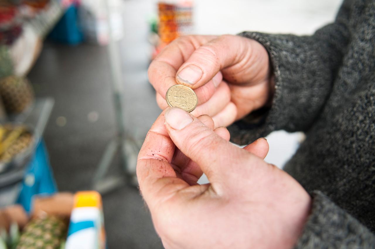 Wochen-Markttag in Refrath, Bergisch Gladbach, am 7.5.0210, fotografiert von Ulla Franke. Bauer Vogel betrachtet ein slovenisches 50 Cent Stück und fragt sich, welchen Weg dieses schon hinter sich hat. Man sieht seine Hände und das Geldstück.