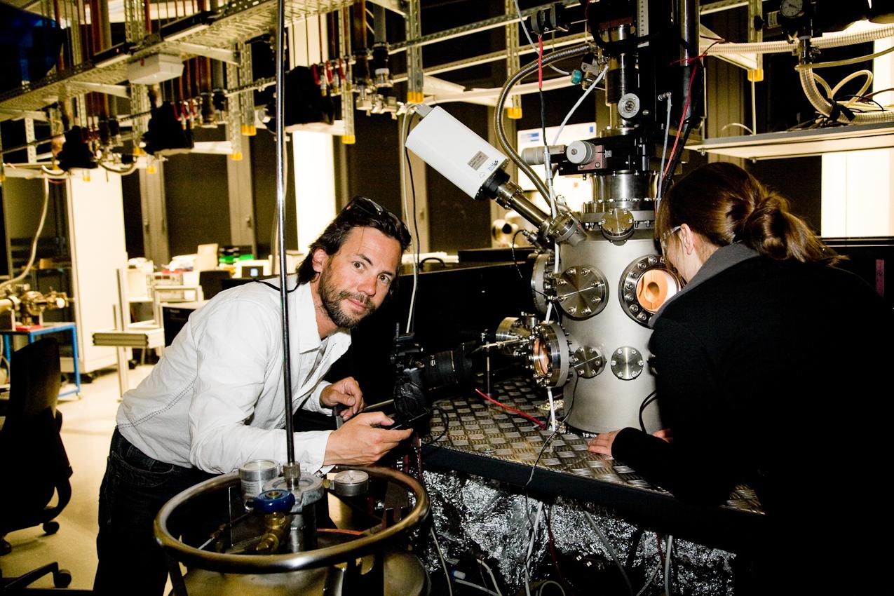 """Eric Lichtenscheidt: 7. Mai 2010: Universität Duisburg-Essen, Campus Duisburg, Fachbereich Physik:  Der Bildjournalist Eric Lichtenscheidt in einem Labor der Arbeitsgruppe von Prof. Horn von Hoegen. Die Arbeitsgruppe wird von der Deutschen Forschungsgemeinschaft (DFG) im Sonderforschungsbereich 616 """"Energiedissipation an Oberflächen"""" unterstützt. Mittels Laserpulsen werden die Nanostrukturen von verschiedenen Stoffen verändert und diese Veränderung beobachtet. Die """"Sonnenbrille"""" ist eine Laserschutzbrille. Photos von Dipl. Phys. Annika Kalus."""