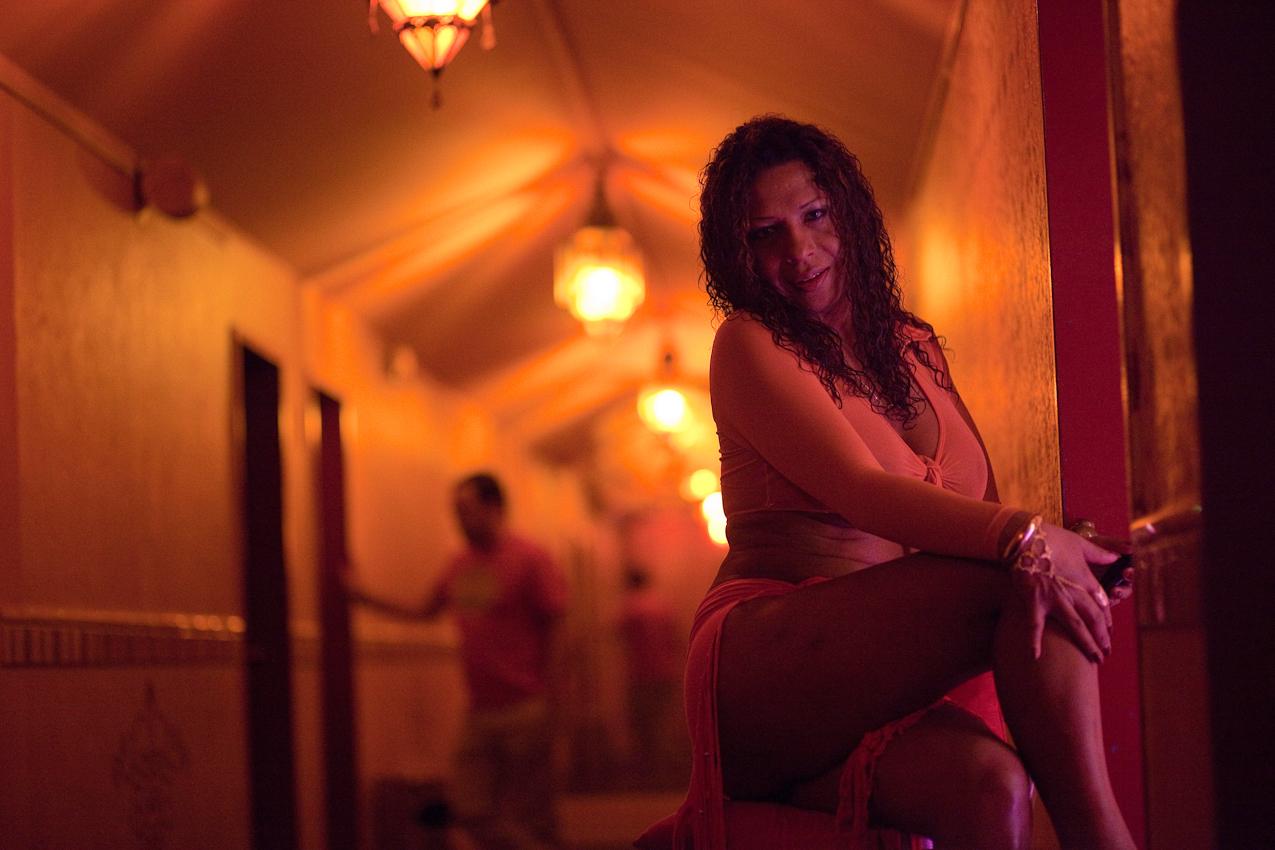 Die transsexuelle Priscila wartet im Gang der 7. Etage auf Kunden, während ein Herr im Hintergrund mit einer Kollegin spricht.