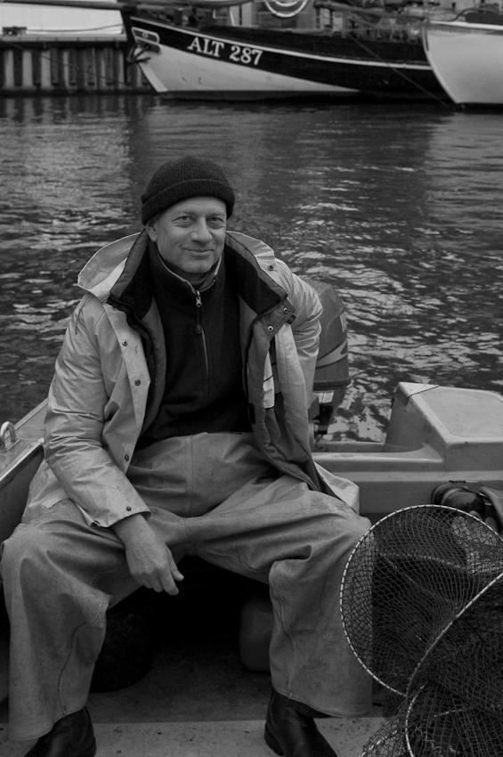 Workshop Photograph Christian Kaiser im Boot des Fischers Olaf Jensen in der Hafencity. Hier sind die Rollen von Fotograf und Fischer vertauscht.