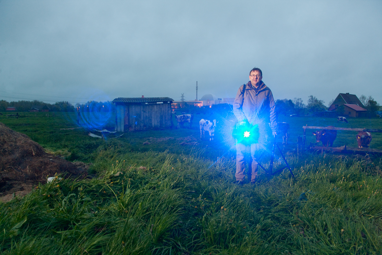 """Making of, Martin Jehnichen mit seinem """"Waterlines"""" Laser / Ilse Mross und ihr Sohn Carsten bewirtschaften ihren Bauernhof direkt neben dem Kernkraftwerk Brokdorf an der Elbe. Am Ende des Tages bekommen die Kälber noch einmal Futter, dann ist Feierabend. Die blaue Linie simuliert den gestiegenen Meerespiegel am Ende des Jahrhundert, wie er von Klimaexperten wegen des Klimawandels vorhergesagt wird. Das Bild ist Teil einer Serie """"Waterlines"""" die sich mit den Folgen eines weltweiten Meeresspiegelanstiegs beschäftigt."""