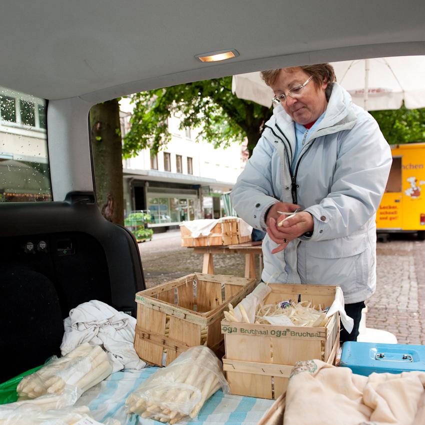 Helga Bader, seit 17 Jahren während der Spargelsaison 2x wöchentlich auf dem Werderplatz. Der Spargel wird für die Kunden vor Ort in der offenen Heckklappe des Autos geschält.