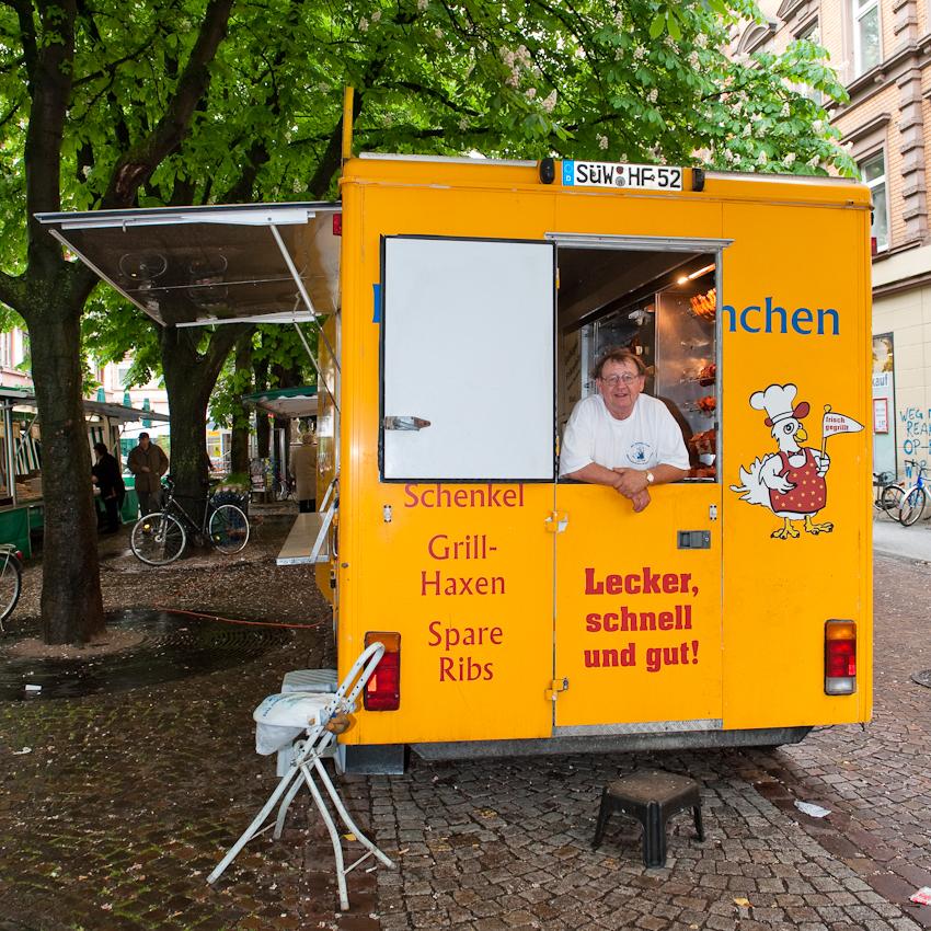 """""""Der Hühner Fred"""", Freitagmorgen um zwanzig vor elf, macht Pause (und beobachtet die Fotografin bei der Arbeit). Mit seinem Wagen ist er jeden Freitag auf dem Werderpaltz in Karlsruhe."""